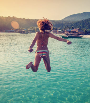 girl jumping from a pier into the sea, in the rays of the setting sun